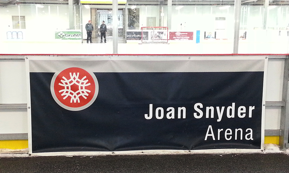 vinyl banner sign hung in a hockey rink