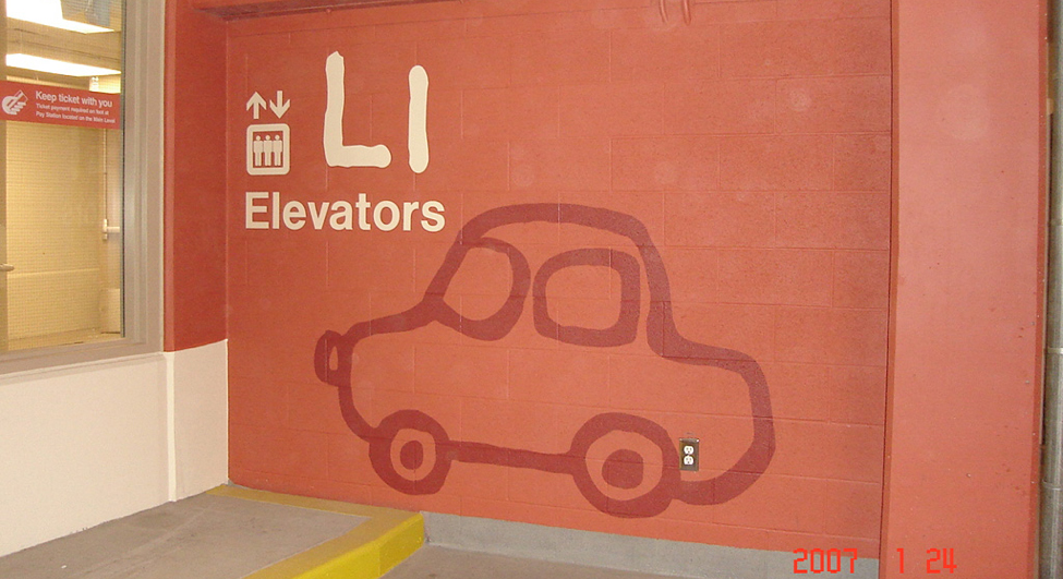 Example of parking lot sign that uses numbers, colors and shapes to help wayfinding