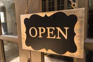 "wooden board sign, with curved gold trim, that says ""open,"" from a restaurant"